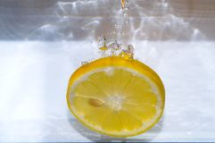 Lemon slice splashing Stock Images