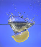 A lemon slice splashing into water. With a blue background Royalty Free Stock Images