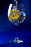 Lemon slice thrown into a glass of water Stock Photos