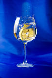 Lemon slice thrown into a glass of water Royalty Free Stock Photography