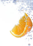Lemon slice in water. Close-up of lemon slice in clear water with bubbles stock image