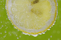 Lemon slice in water with bubbles Royalty Free Stock Images