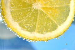 Lemon slice. Slice of lemon and water bubbles Royalty Free Stock Photos