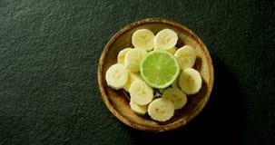 Lemon and sliced banana in a bowl 4k. Overhead view of lemon and sliced banana in a bowl 4k stock video