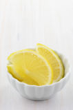 Lemon slices. In little white dish on rustic background with room for your text Stock Photography