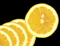 Lemon Slices. One lemon slice and four overlapping partial lemon slices on a black background royalty free stock image