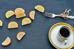 Lemon slices and cup of coffee. Slice of moist lemon bundt cake  and   lemon and orange slices  on black slate Royalty Free Stock Photography