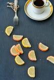Lemon slices and cup of coffee. Slice of moist lemon bundt cake  and   lemon and orange slices  on black slate Stock Images