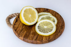 Lemon and slices on cutting board on light background Stock Photo