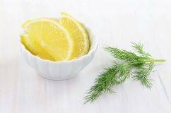 Lemon slices and dill. Slices of fresh lemon in pretty bowl with sprig of dill on rustic background Stock Photography