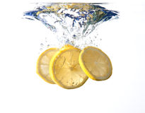 Lemon slices fall into water Royalty Free Stock Images