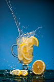 Lemon slices falling into a glass of lemonade and a big splash on a blue background.  Royalty Free Stock Image