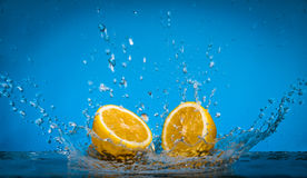 Lemon Slices falling for water with a big splash on blue background. Stock Photography