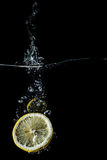 Lemon slices falling into the water close-up, macro, splash, bubbles, isolated Royalty Free Stock Image