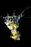 Lemon slices falling into the water close-up, macro, splash, bubbles, isolated Royalty Free Stock Images