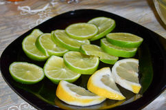 Lemon. Slices of lemon and lime on a black plate Royalty Free Stock Image