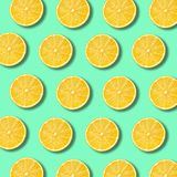 Lemon slices pattern on vibrant green color background. Lemon slices pattern on light vibrant green color background. Minimal flat lay food texture royalty free stock photos