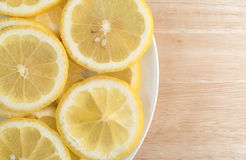 Lemon slices on a plate atop a wood cutting board Stock Photos