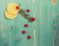 Lemon slices, raspberry and rosemary on turquoise wooden desk. Lemon slices, raspberry and rosemary on turquoise colored wooden desk Stock Image