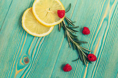 Lemon slices, raspberry and rosemary on turquoise wooden desk. Lemon slices, raspberry and rosemary on turquoise colored wooden desk, close-up Stock Photos