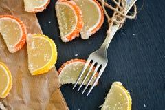 Lemon slices. Slice of moist lemon bundt cake  and   lemon and orange slices  on black slate Stock Photos