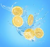Lemon slices in water splash on a blue background stock photo