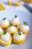 Lemon sorbet or ice cream inside fresh lemons. Decorated with mint leaves on big white plate stock photos