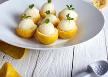 Lemon sorbet or ice cream inside fresh lemons. Decorated with mint leaves on big white plate royalty free stock images