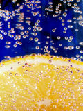 Lemon In Sparkling Water 2. Lemon slice in sparkling water with a blue background royalty free stock photo
