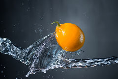 Lemon and splash of water on grey background.  Royalty Free Stock Images