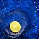 Lemon splashing blue water Royalty Free Stock Photo
