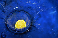 Lemon splashing blue water Royalty Free Stock Image