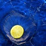Lemon splashing blue water Royalty Free Stock Photos