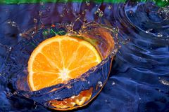 Lemon splashing in blue water Stock Photos
