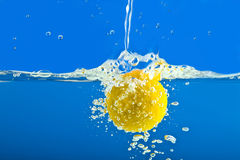 Lemon splashing into blue water Stock Photos