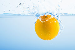 Lemon splashing into blue water Stock Images