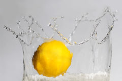 Lemon splashing into clear water on white background. Royalty Free Stock Photography