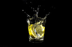Lemon splashing in glass. Isolated on a black background Stock Photo