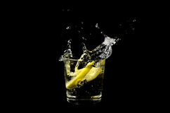Lemon splashing in glass. Isolated on a black background Stock Photos