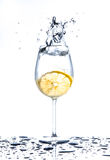 Lemon splashing into glass of water on white background Stock Images