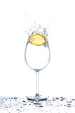 Lemon splashing into glass of water on white background Royalty Free Stock Images