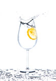 Lemon splashing into glass of water on white background Royalty Free Stock Image
