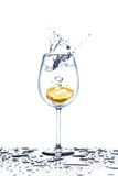 Lemon splashing into glass of water on white background Royalty Free Stock Photo