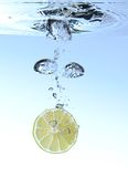 Lemon splashing in water. Isoleted in a blue background royalty free stock photography