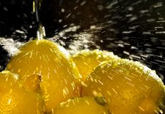 Lemon Spray. Drops of water flying in the sunlight as they fall on the lemons stock images