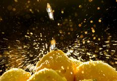 Lemon Spray. Drops of water flying in the sunlight as they fall on the lemons stock photo