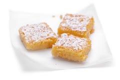 Lemon Squares. Three lemon squares on paper on white background stock photos