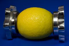 Lemon squeeze. A fresh, whole lemon appearing to be squeezed.  Blue background Royalty Free Stock Photos