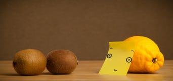 Lemon with post-it note looking at kiwis. Lemon with sticky post-it note watching at kiwis royalty free stock photo