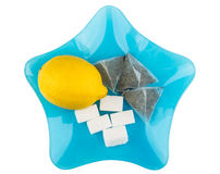 Lemon, sugar and tea bags in blue glass plate Royalty Free Stock Photo